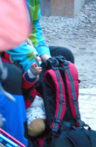 Facet próbuje dzieciaka wepchnąć do nosidełka, pomimo jego wyraźnych sprzeciwów